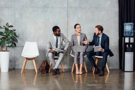 Photo pour Gens d'affaires multiculturelles assis, à l'aide d'appareils numériques et avoir des discussions dans la salle d'attente - image libre de droit