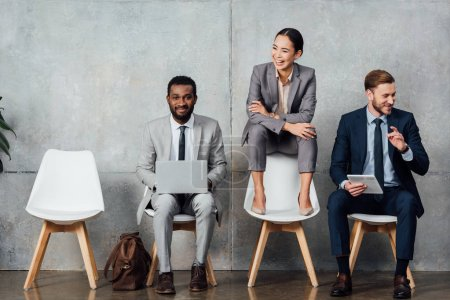 Photo for Smiling multiethnic businessmen using digital devices while businesswoman sitting on chair with arms crossed in waiting hall - Royalty Free Image