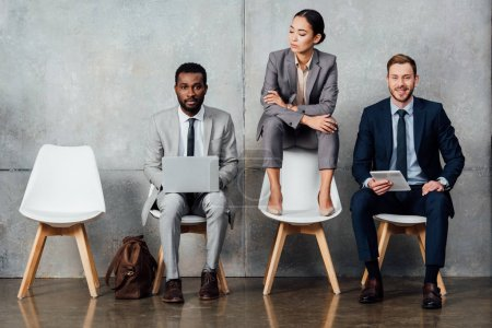Photo for Multiethnic businessmen using digital devices while businesswoman sitting on chair with arms crossed in waiting hall - Royalty Free Image