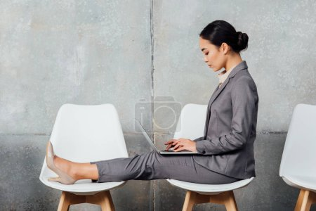 asian businesswoman in formal wear sitting on chairs and using laptop in waiting hall