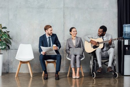 smiling multicultural businesspeople sitting and listening while african american man in wheelchair playing guitar in waiting hall