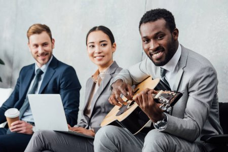 multicultural businesspeople sitting and listening while african american man playing guitar in waiting hall