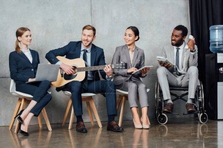multicultural businesspeople using digital devices while businessman playing acoustic guitar in waiting hall