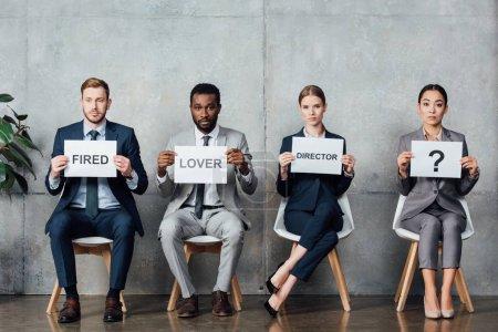 """Photo pour Des hommes d'affaires multiethniques tenant des cartes avec """"amant"""", """"réalisateur"""", mots """"virés"""" et point d'interrogation dans la salle d'attente - image libre de droit"""