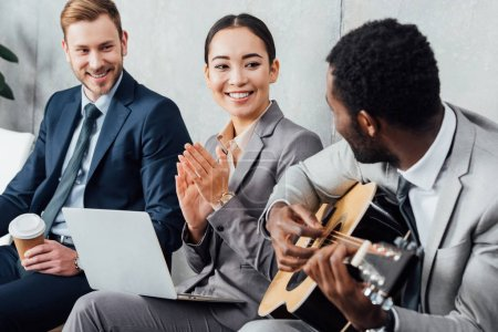 smiling multicultural businesspeople sitting and listening while african american man playing guitar in waiting hall