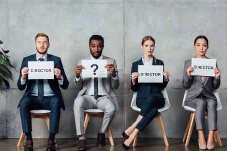 """Photo pour Des hommes d'affaires multiethniques tenant des cartes avec des mots de """"réalisateur"""" et un point d'interrogation dans la salle d'attente - image libre de droit"""