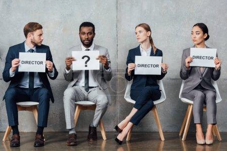 """Photo pour Des gens d'affaires multiethniques assis et tenant des cartes avec des mots de """"réalisateur"""" et un point d'interrogation dans la salle d'attente - image libre de droit"""