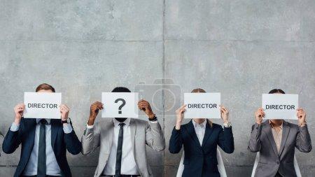 """Photo pour Des hommes d'affaires multiethniques tenant des cartes avec des mots de """"réalisateur"""" et un point d'interrogation devant des visages dans une salle d'attente - image libre de droit"""