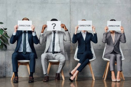 multiethnic businesspeople sitting and holding cards with 'director' words and question mark in front of faces in waiting hall
