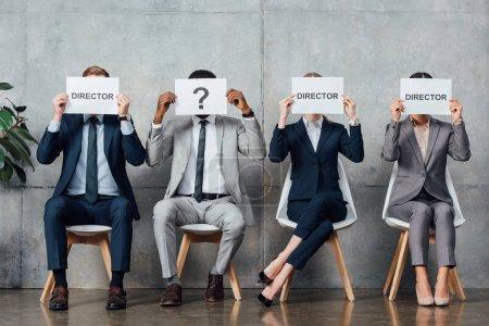 """Photo pour Des gens d'affaires multiethniques assis et tenant des cartes avec des mots de """"réalisateur"""" et un point d'interrogation devant des visages dans la salle d'attente - image libre de droit"""