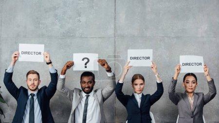 """Photo pour Des gens d'affaires multiethniques tenant des cartes avec des mots de """"réalisateur"""" et un point d'interrogation en regardant la caméra - image libre de droit"""