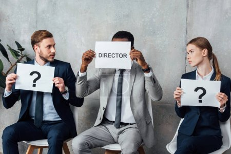 multiethnic businesspeople holding cards with 'director' word and question marks in waiting hall