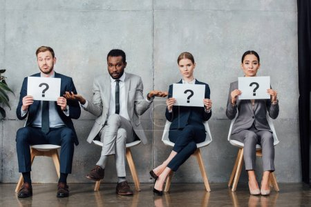 multiethnic businesspeople holding cards with question marks in waiting hall