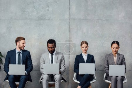 Photo for Multiethnic businesspeople sitting on chairs and using laptops in waiting hall - Royalty Free Image