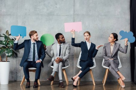 Photo for Multiethnic businesspeople holding speech bubbles and thought bubble while sitting in waiting hall - Royalty Free Image