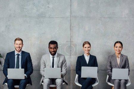 Photo pour Gens d'affaires multiethniques heureux assis sur des chaises et à l'aide d'ordinateurs portables dans la salle d'attente - image libre de droit
