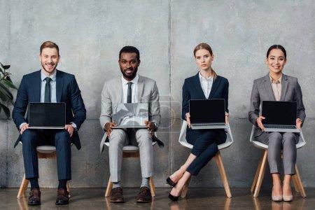 Photo pour Gens d'affaires multiethniques assis sur des chaises et la tenue des ordinateurs portables avec écran blanc dans la salle d'attente - image libre de droit