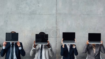 businesspeople sitting on chairs and holding laptops with blank screen in front of faces in waiting hall