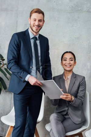 smiling multiethnic businesspeople holding folder during meeting in office
