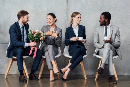 Photo for Multiethnic businesspeople sitting with flowers and coffee in office - Royalty Free Image