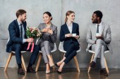 multiethnic businesspeople sitting with flowers and coffee in office