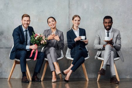 Photo for Smiling multiethnic businesspeople sitting with flowers and coffee in office - Royalty Free Image