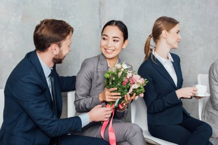 businessman presenting flowers to beautiful asian businesswoman in office