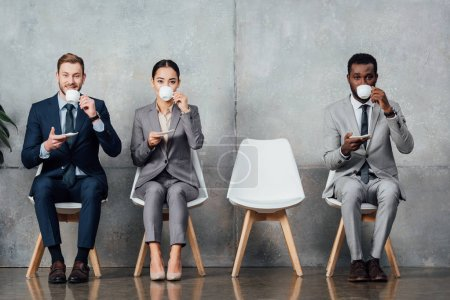 multiethnic businesspeople drinking coffee while sitting on chairs in waiting hall