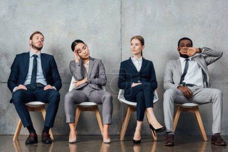 Photo pour Businesspeople multiethnique s'ennuie, assis sur des chaises dans la salle d'attente - image libre de droit