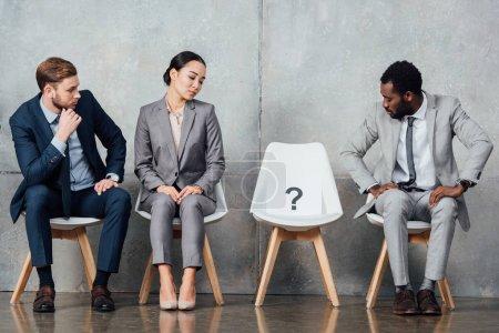 Foto de Empresarios multiétnicos mirar tarjeta con signo de interrogación en silla en sala de espera - Imagen libre de derechos