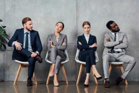 dissatisfied multiethnic businesspeople sitting on chairs with arms crossed in waiting hall