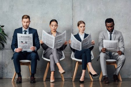 multiethnic businesspeople sitting on chairs and reading newspapers in waiting hall