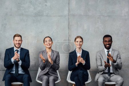 multiethnic businesspeople sitting on chairs and applauding in waiting hall