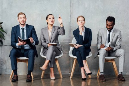 asian businesswoman raising hand while having meeting with multiethnic colleagues in office