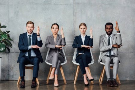 serious multiethnic businesspeople sitting on chairs with raised hands ready to answer in waiting hall