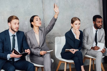 businesswoman raising hand while focused multiethnic businesspeople sitting on chairs with notebooks
