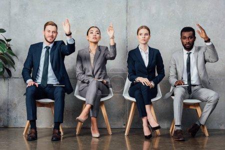 Foto de Empresarios multiétnicos sentado en una silla con las manos levantadas listas para responder en la sala de espera - Imagen libre de derechos