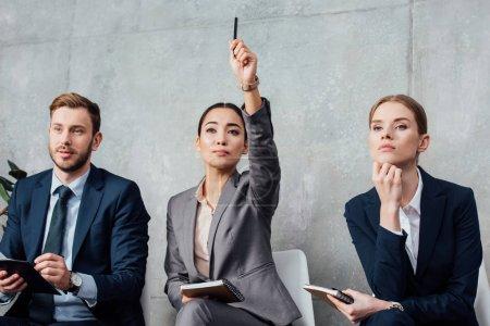 Foto de Empresaria enfocada levantar mano teniendo reuniones con sus colegas en la oficina - Imagen libre de derechos