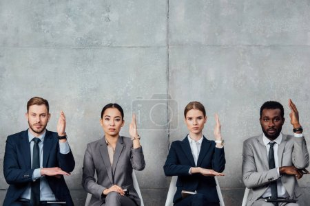 focused multiethnic businesspeople sitting on chairs with raised hands ready to answer in waiting hall