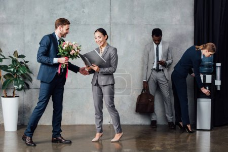 businessman presenting flowers to smiling businesswoman with multiethnic colleagues on background in waiting hall