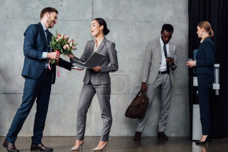 businessman presenting flowers to businesswoman with multiethnic colleagues on background in waiting hall