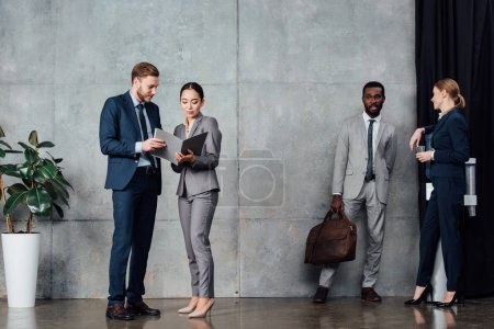 Photo for Multiethnic businesspeople in formal wear talking in waiting hall - Royalty Free Image