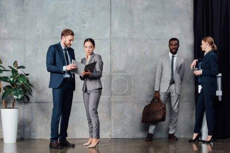 multiethnic businesspeople in formal wear talking in waiting hall