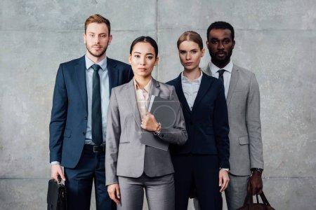 Photo pour Groupe multiethnique ciblé d'hommes d'affaires en tenue formelle posant et regardant la caméra - image libre de droit