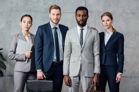 confident multiethnic group of businesspeople in formal wear looking at camera