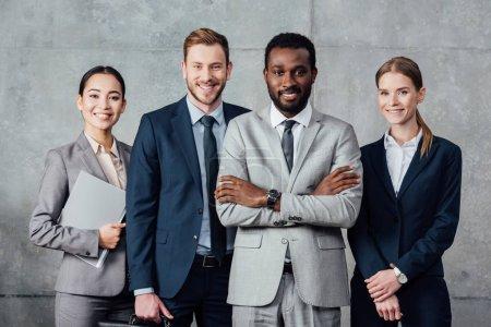Foto de Feliz grupo multiétnico de empresarios en ropa formal posando y mirando a la cámara - Imagen libre de derechos