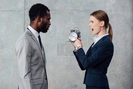 african american businessman looking at yelling businesswoman pointing at clock on grey background