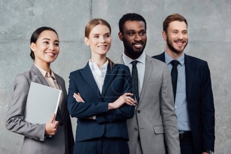 smiling multiethnic group of businesspeople in formal wear posing and looking away