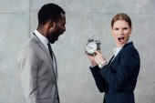 businesswoman looking at camera and pointing at clock while african american businessman shouting on grey background