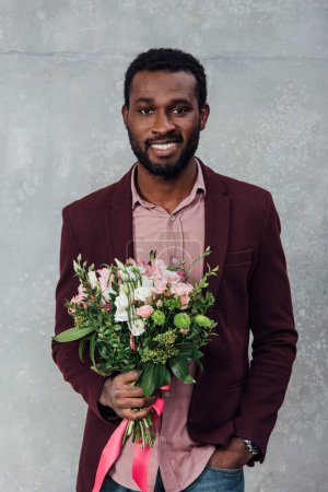 african american man in casual clothes holding flowers and looking at camera on grey background